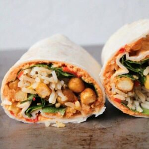 Curried chickpea wrap with red pepper hummus and a tahini drizzle