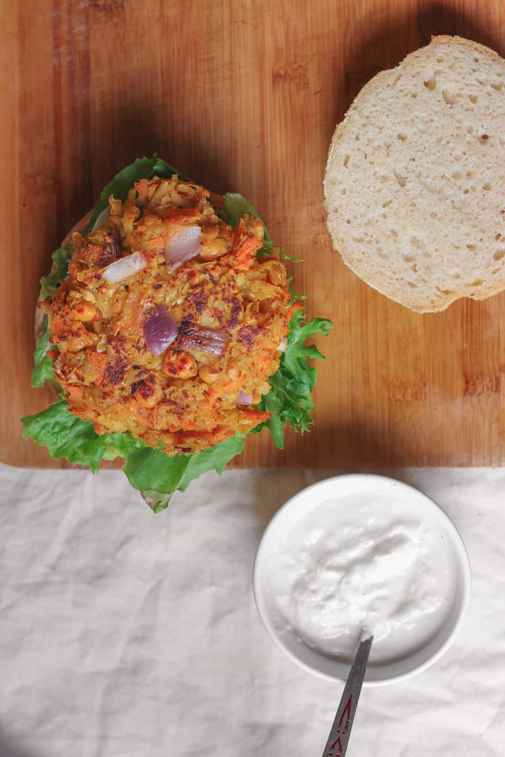 Vegan chickpea fritter burger resting on a table with a bowl of soy yoghurt nearby