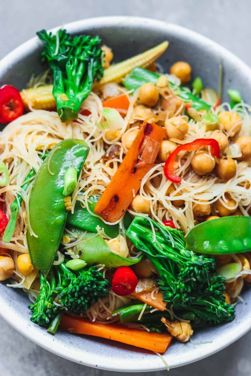 Blue bowl with noodles chickpeas and vegetables