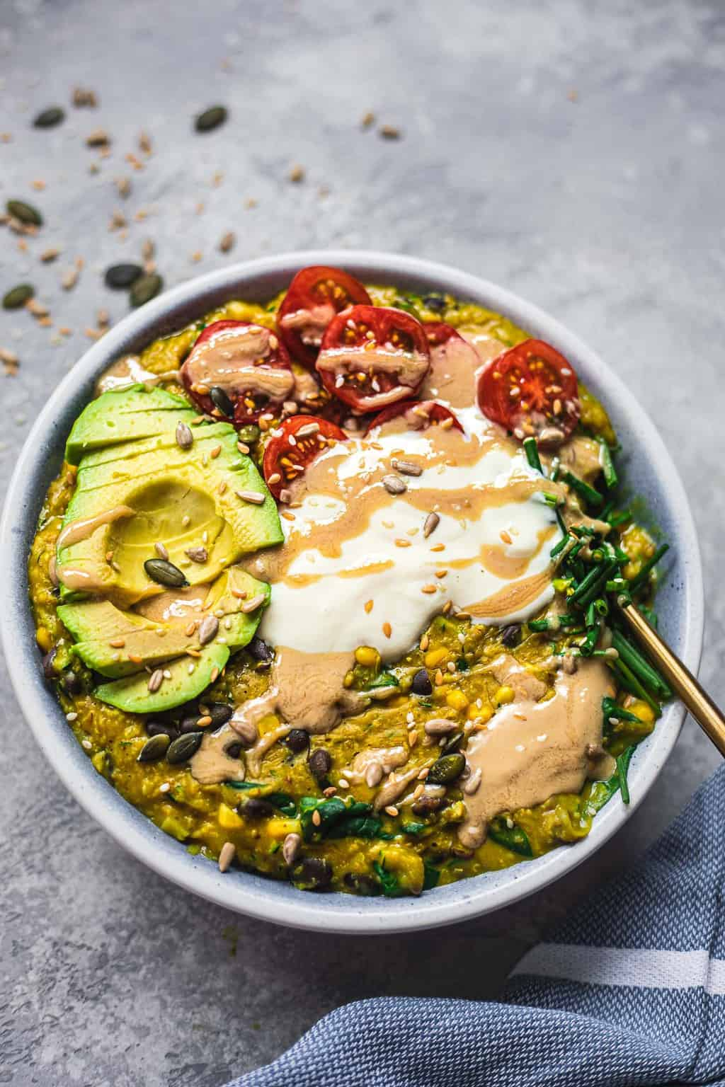 Bowl of vegan oats with avocado and tomatoes