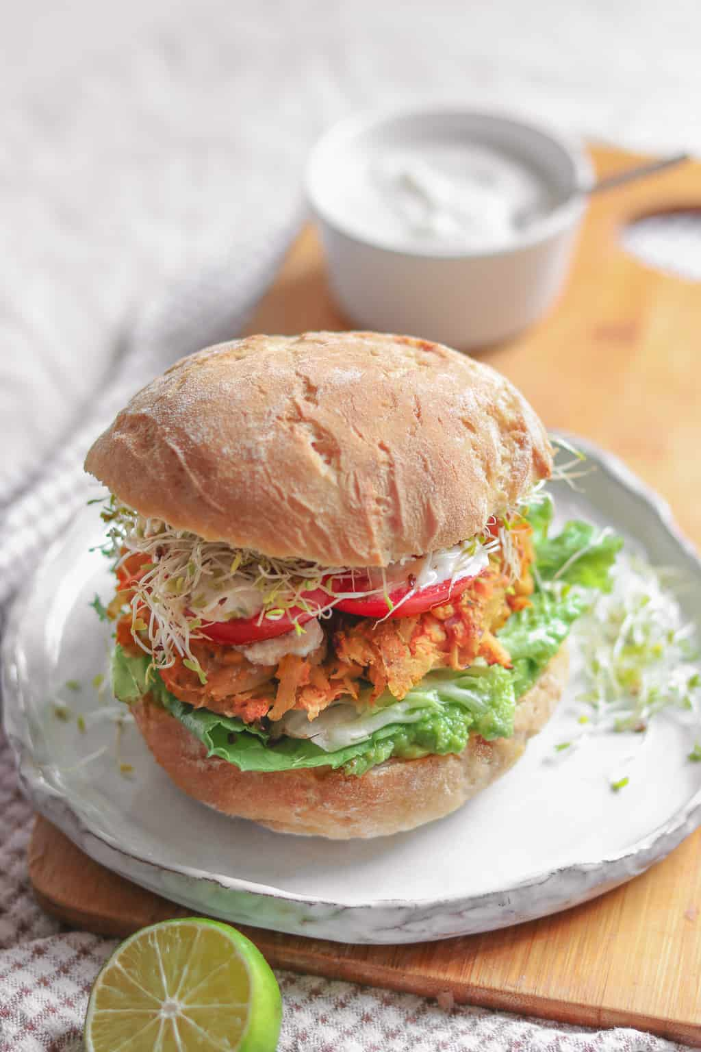 Vegan sandwich with chickpea fritters, avocado, alfalfa sprouts, tomatoes, mixed greens and soy yoghurt on a white plate