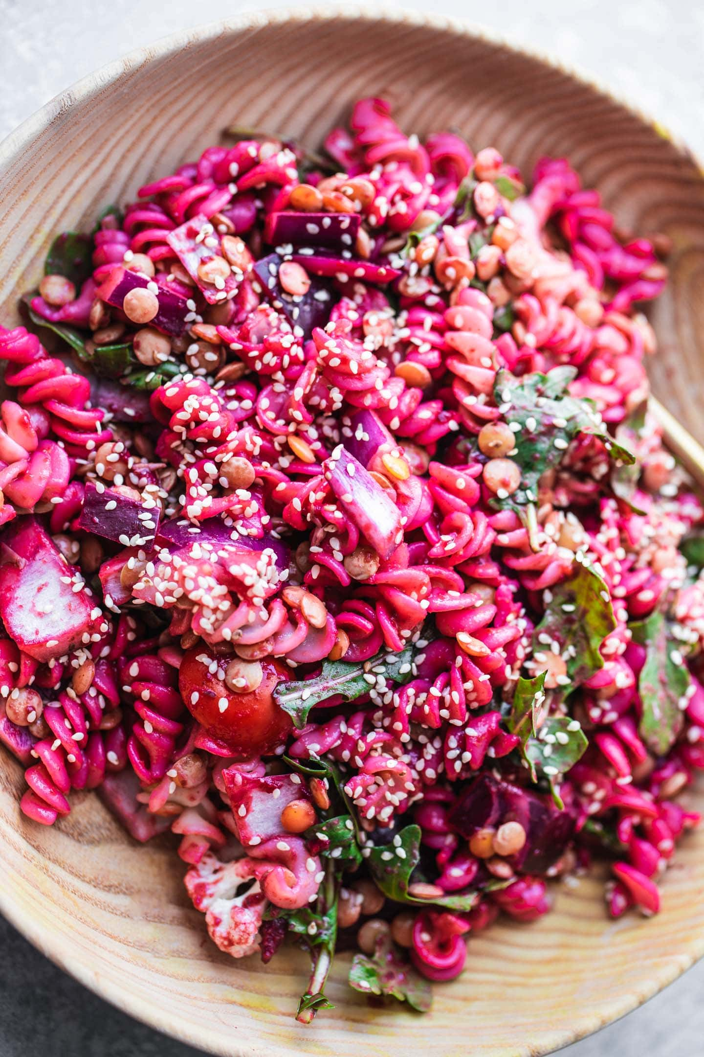 Bowl of beetroot pasta salad with green lentils