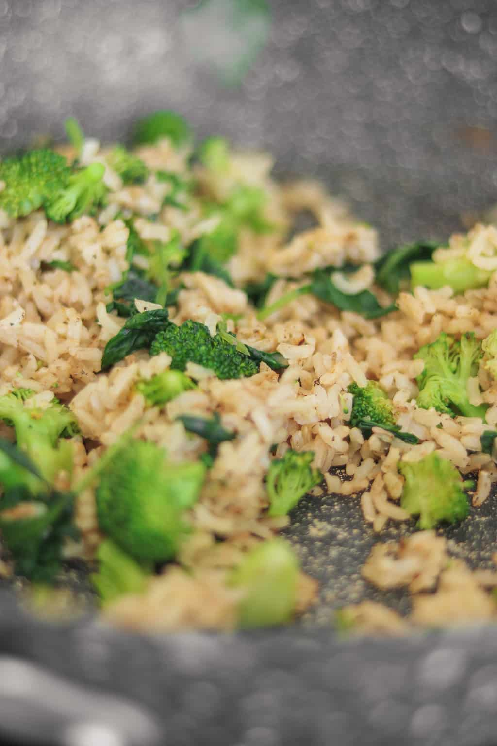 Brown rice, broccoli and spinach in a frying pan