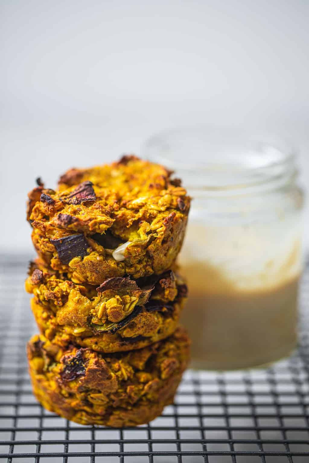Oat and tofu vegan 'egg' muffins on a cooling rack next to a jar of tahini