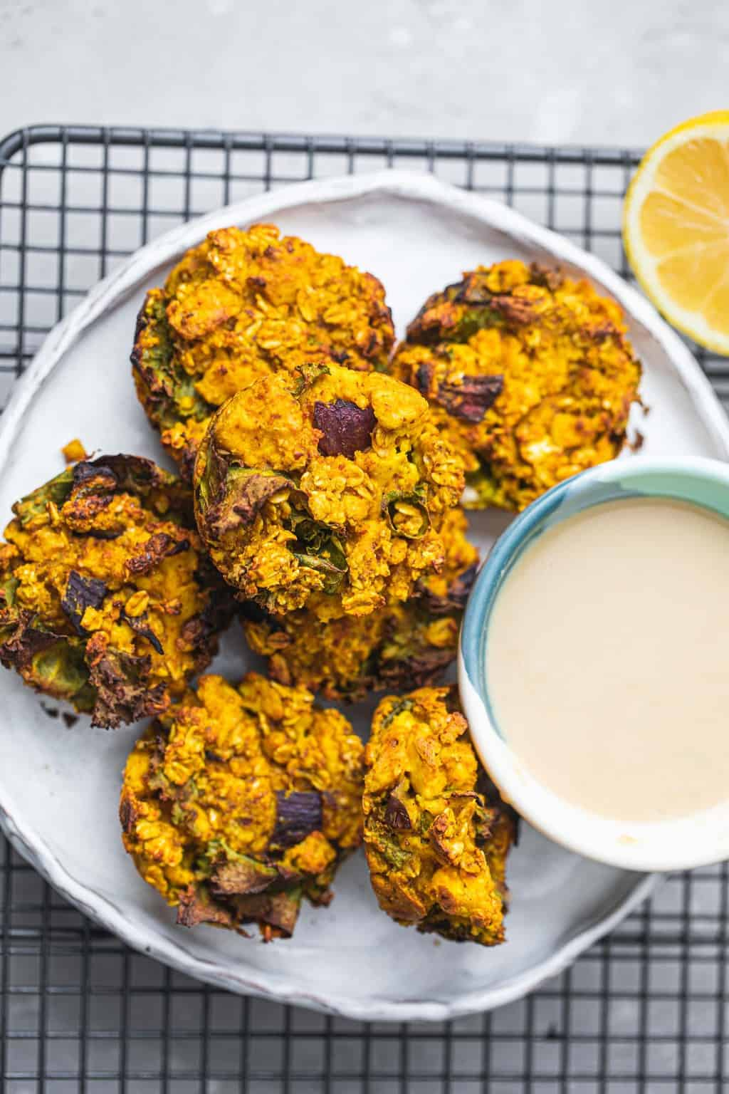Plate of vegan 'egg' muffins next to tahini sauce on a white plate