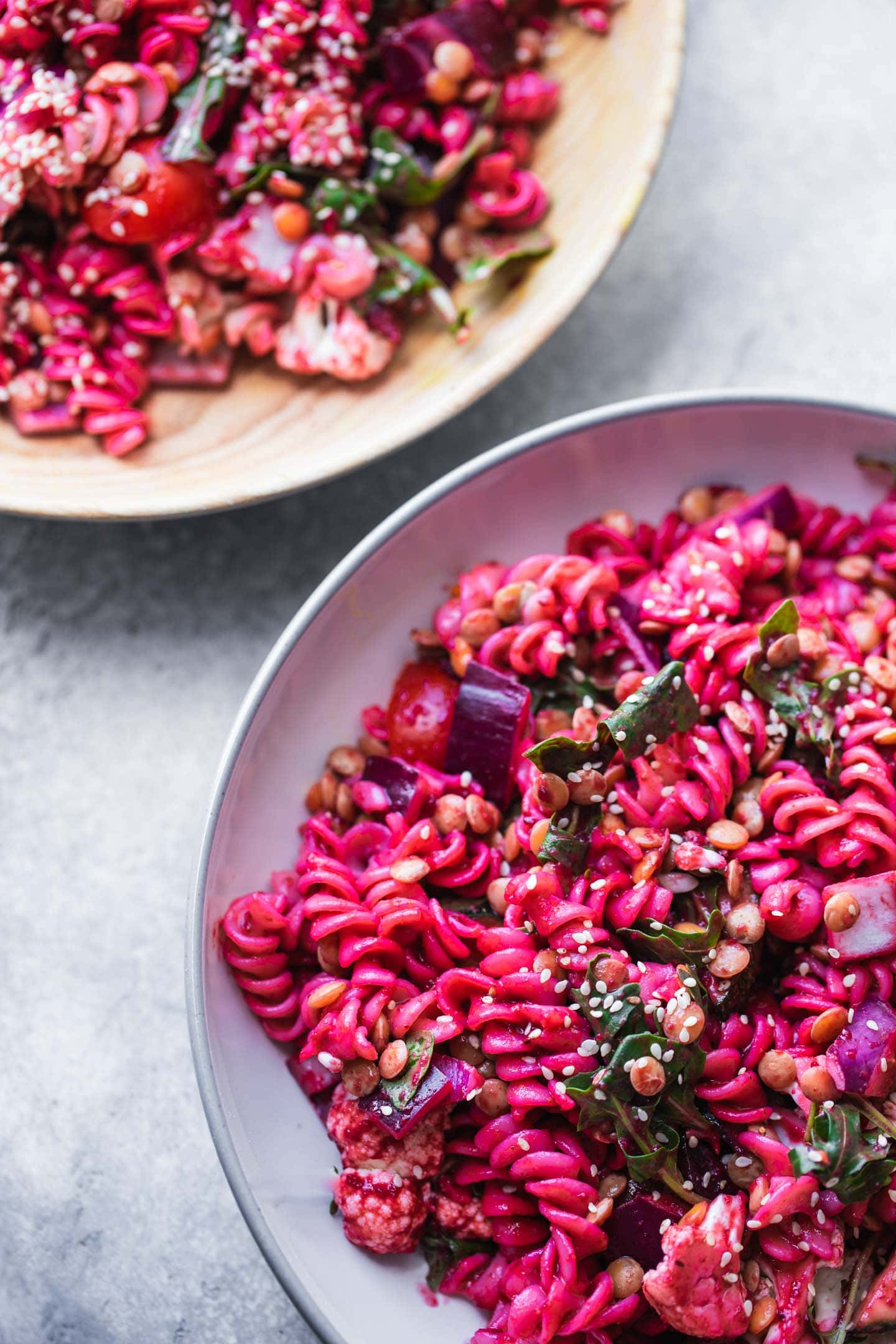 Two bowls of pasta salad with lentils and vegetables