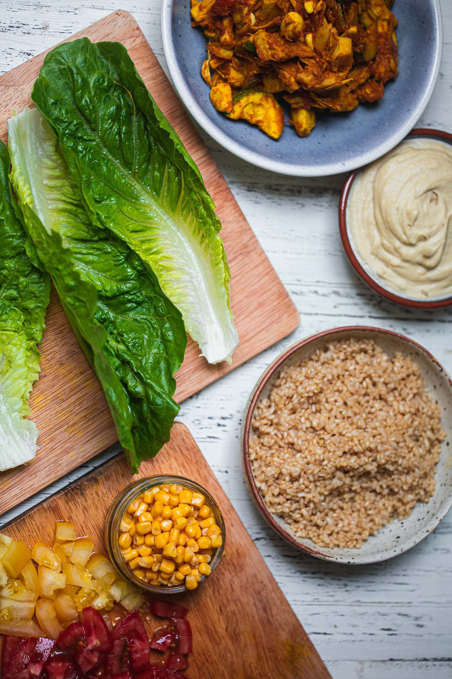 Lettuce leaves on a chopping board with brown rice and jackfruit next to them