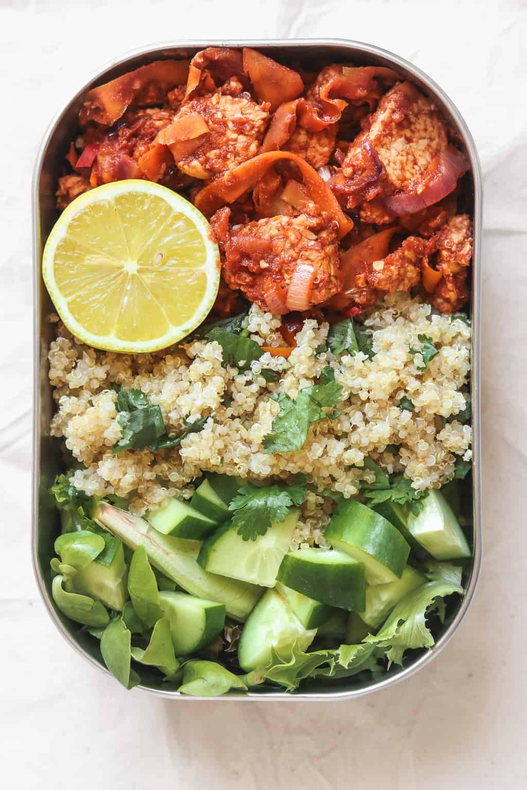 Vegan meal prep lunchbox with quinoa and tempeh in a tomato sauce