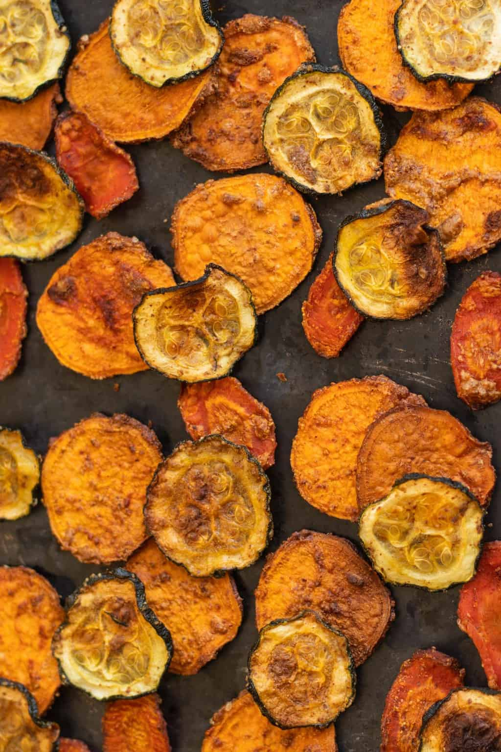 Homemade sweet potato, carrot and zucchini chips on baking sheet