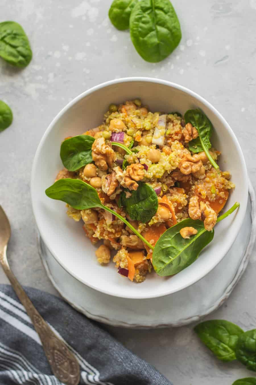 Bowl of vegan chickpea quinoa salad with pumpkin and spinach