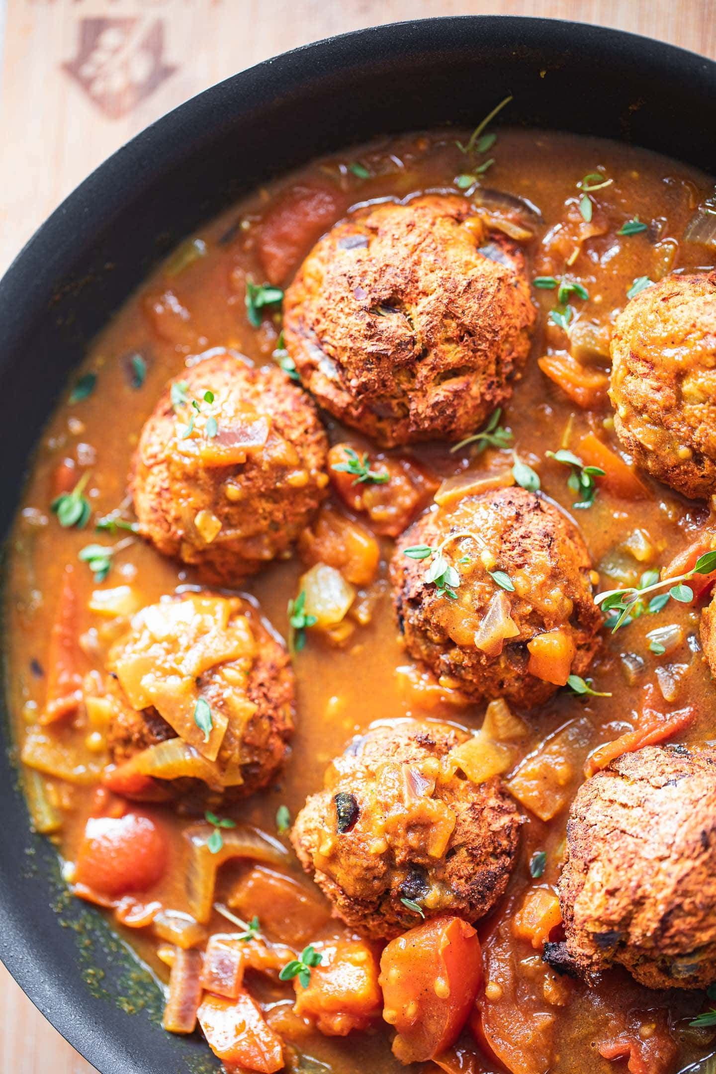 Lentil meatballs in a pan with a curry sauce