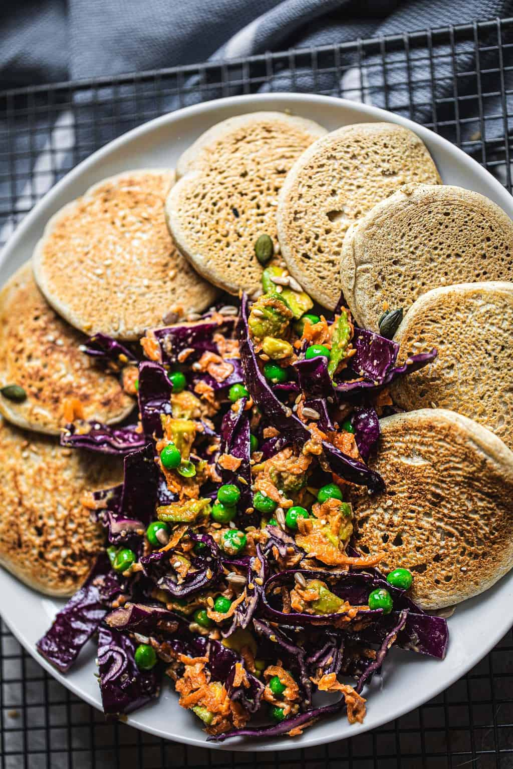 Savoury pancakes on a white plate with a purple cabbage slaw