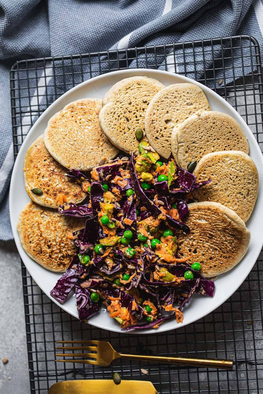Vegan pancakes on a white flat with purple cabbage slaw