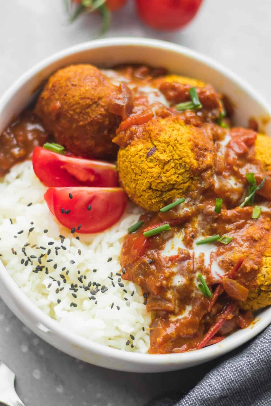 Vegan lentil meatballs in curry sauce over a bed of rice