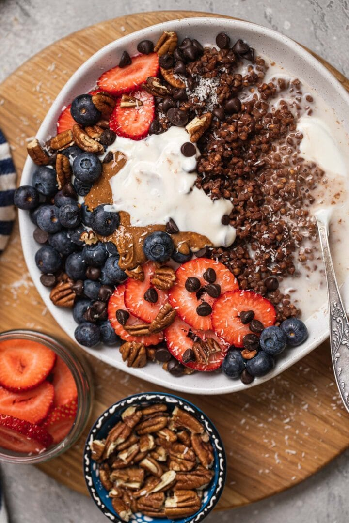 Bowl of buckwheat with vegan yoghurt, peanut butter and berries