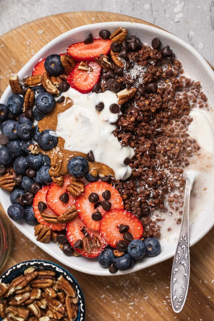 Bowl of chocolate porridge with soy yoghurt, berries and peanut butter