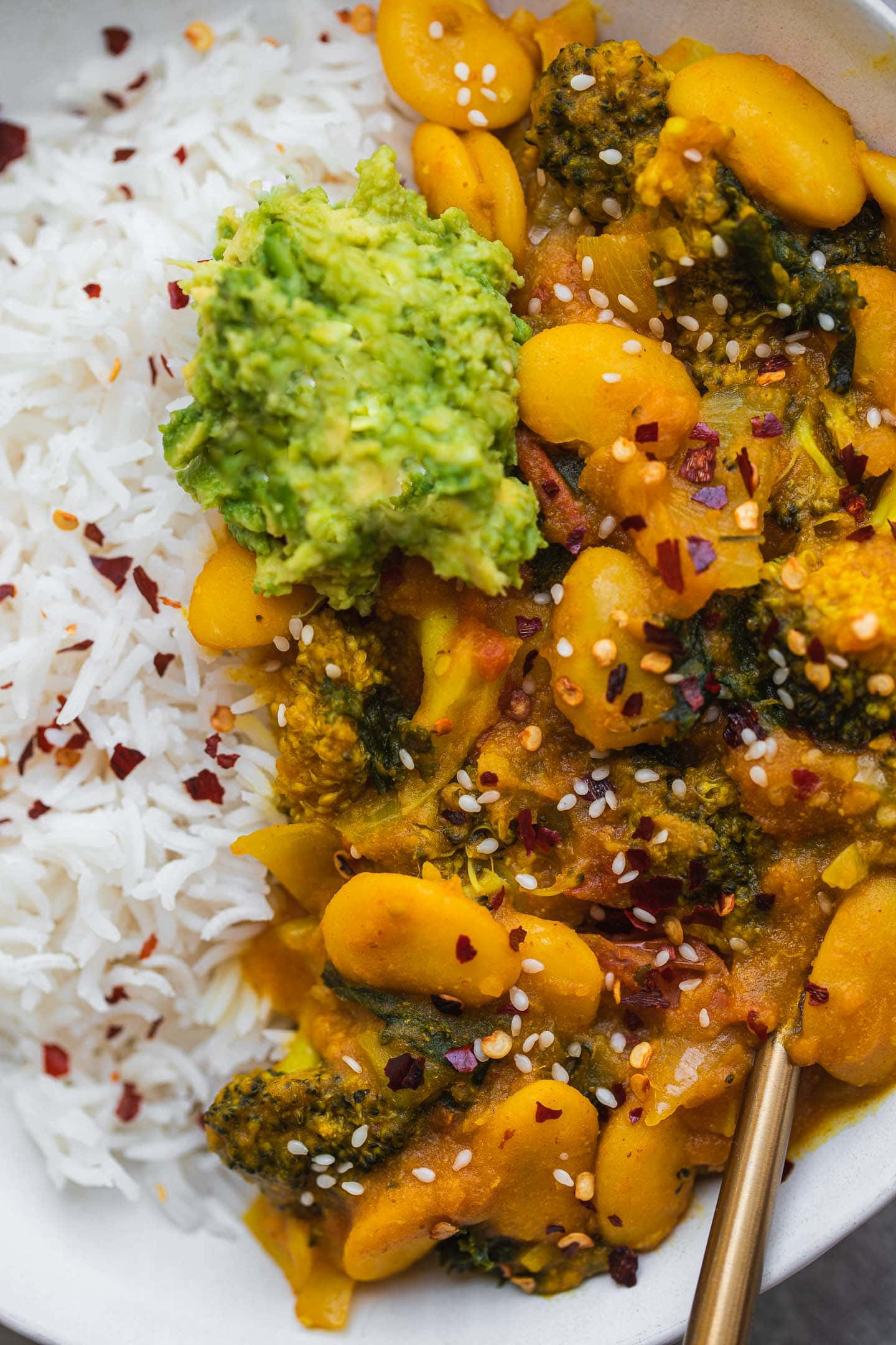 Closeup of butter bean stew with rice and avocado