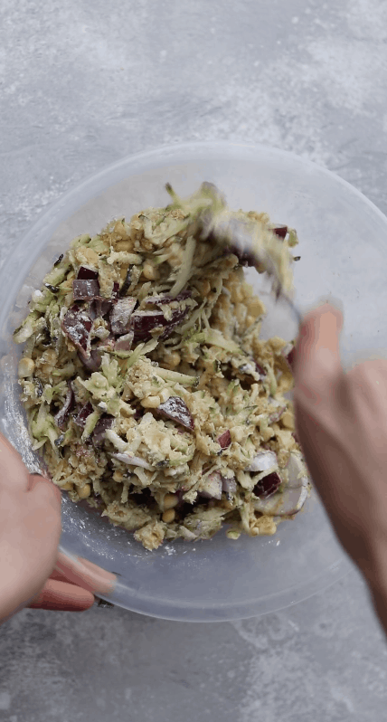 Vegan zucchini fritter ingredients in a mixing bowl