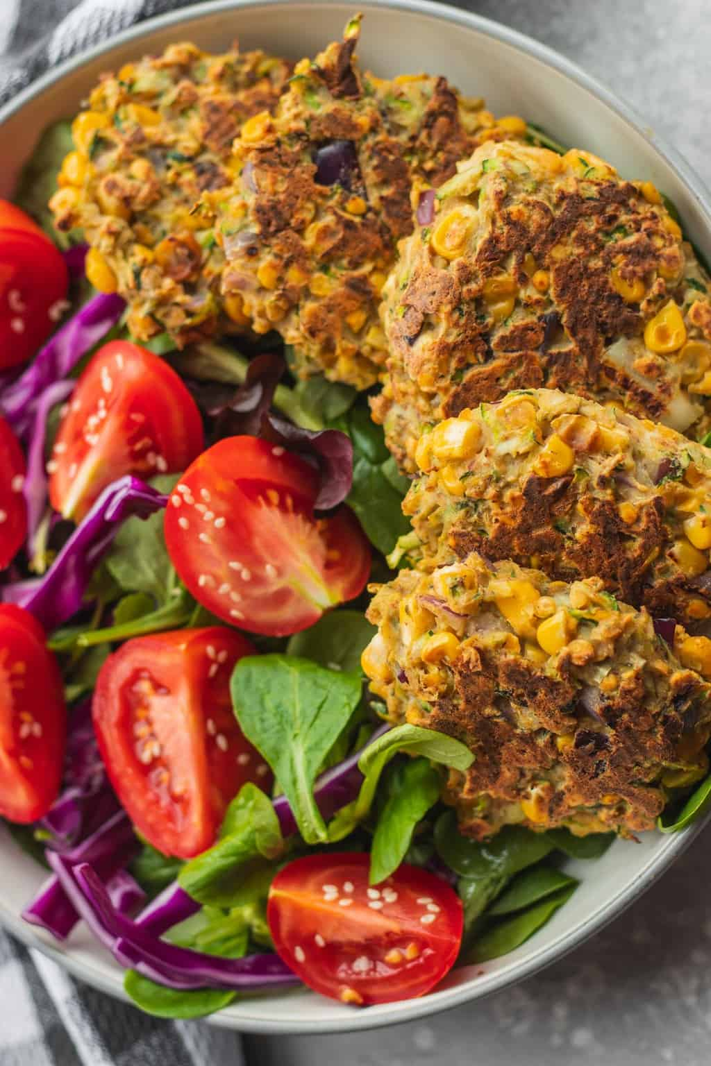 Vegan red lentil zucchini fritters with sweetcorn and a side salad