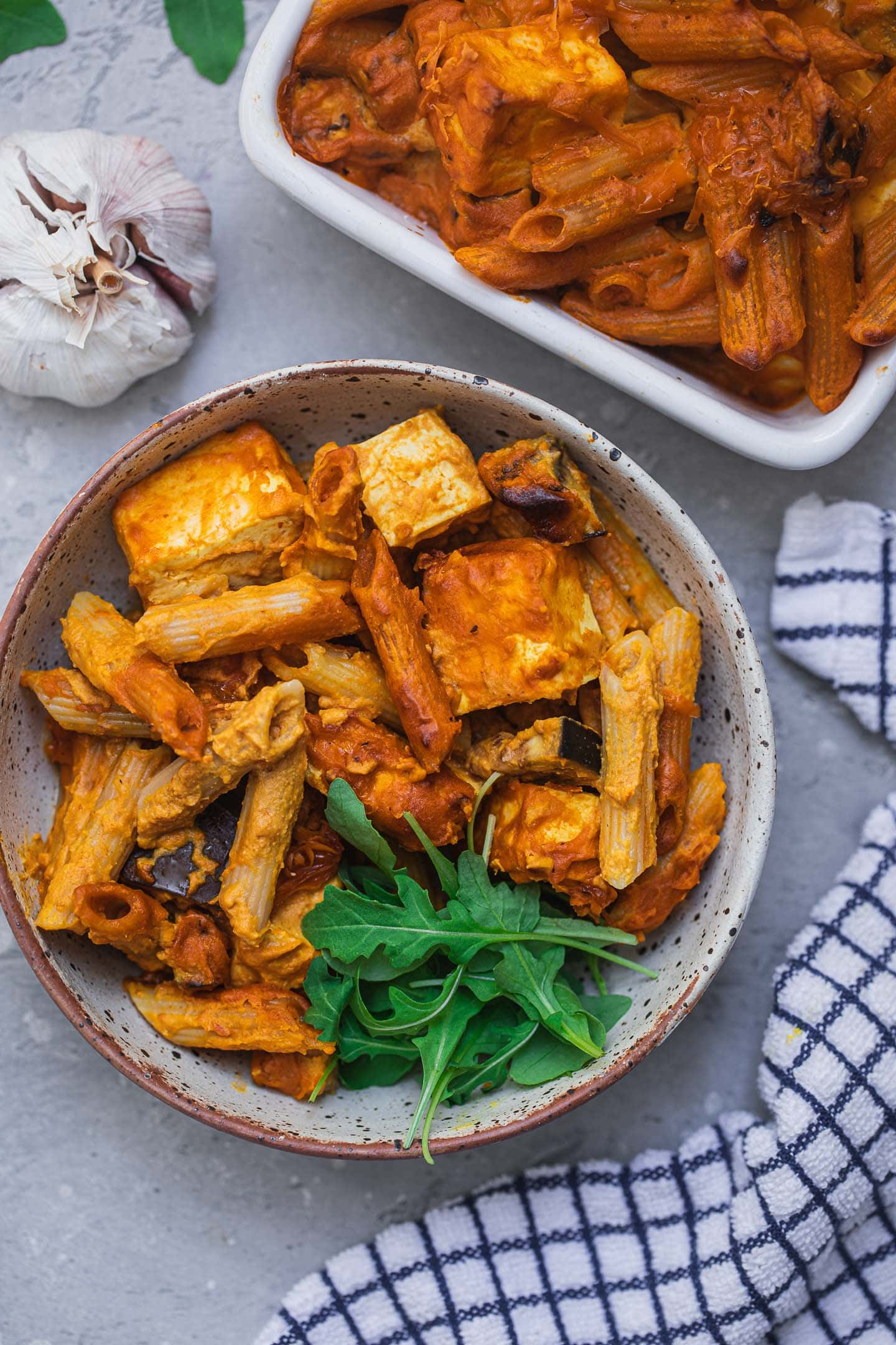 Pasta bake in a bowl with aubergine, tofu and leafy greens