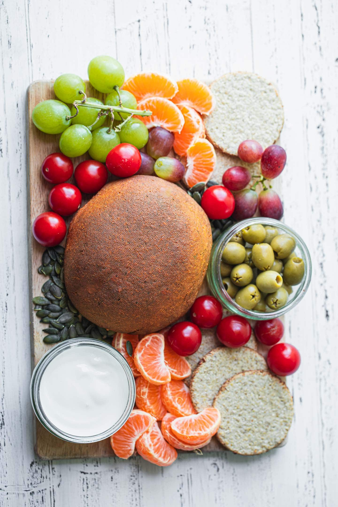 Platter with vegan cheese grapes tomatoes and crackers