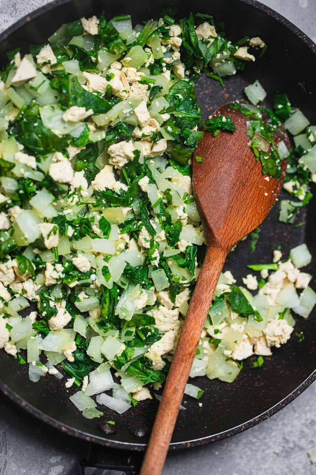 Tofu spinach and onion in a frying pan