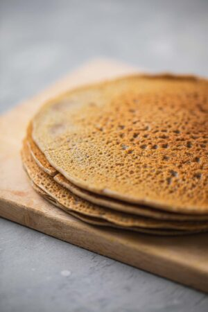 Buckwheat crepes resting on a wooden chopping board
