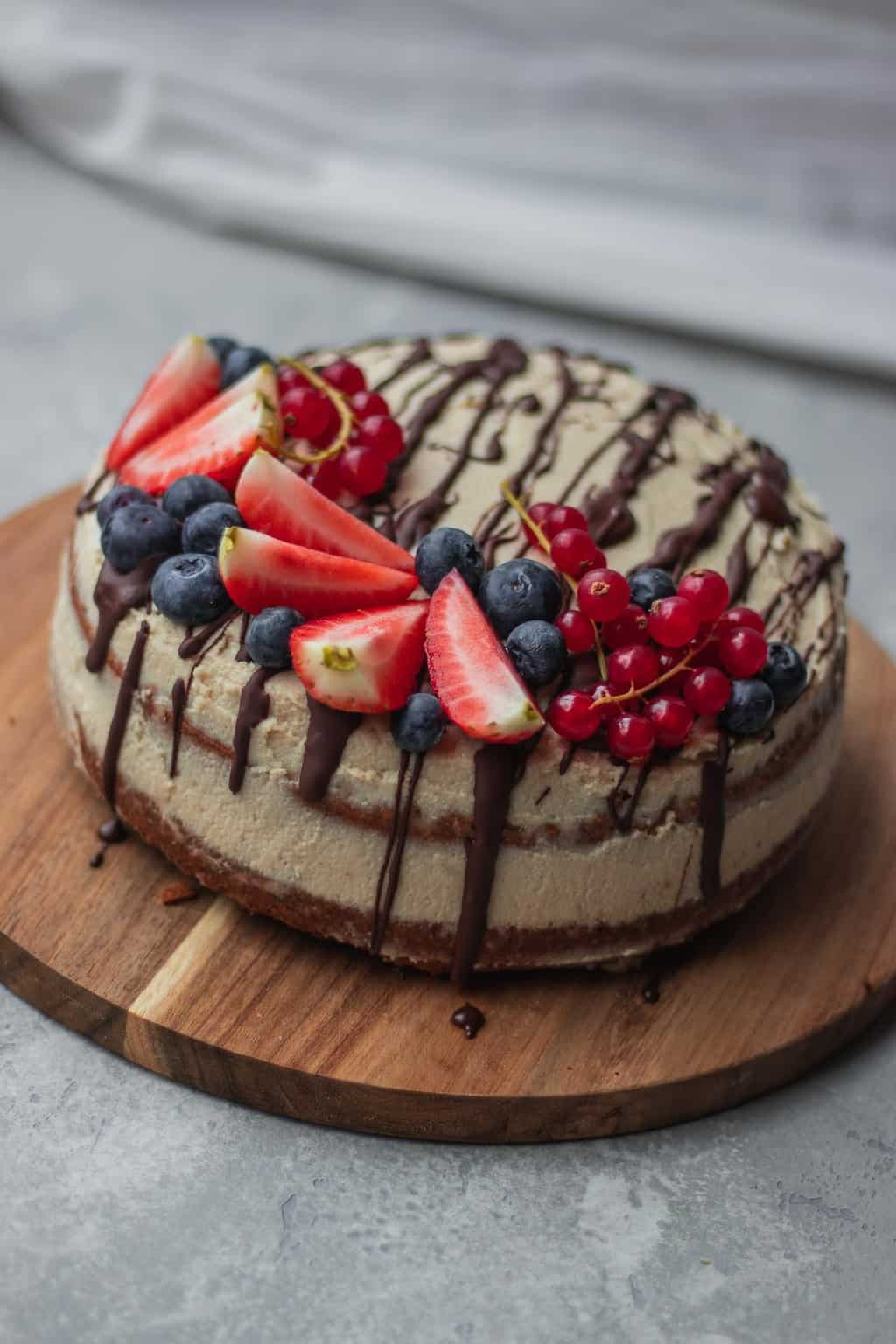 Vegan gingerbread cake with coconut frosting and berries