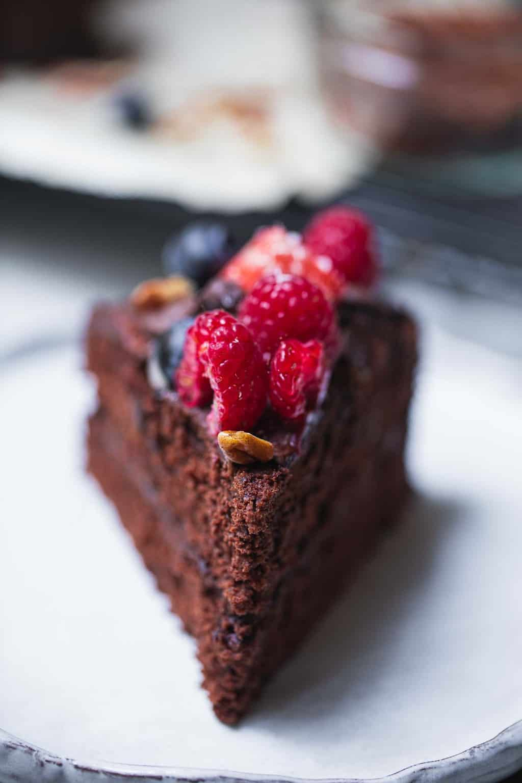 Slice of vegan chocolate cake with berries on a white plate