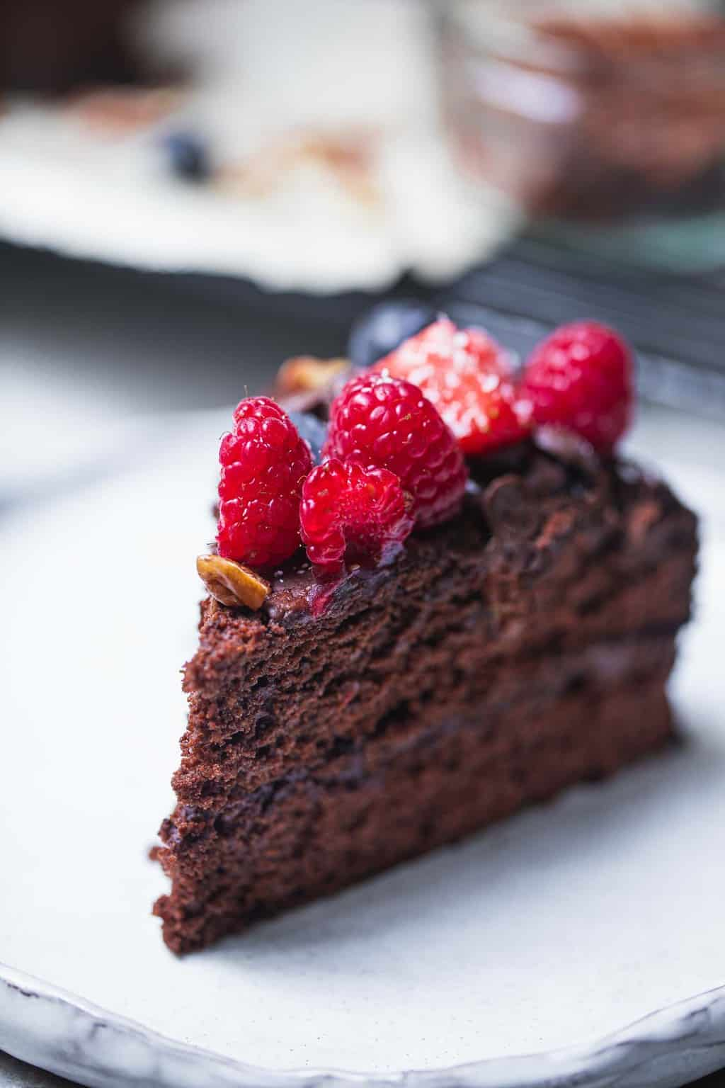 Slice of vegan chocolate cake with berries on a plate