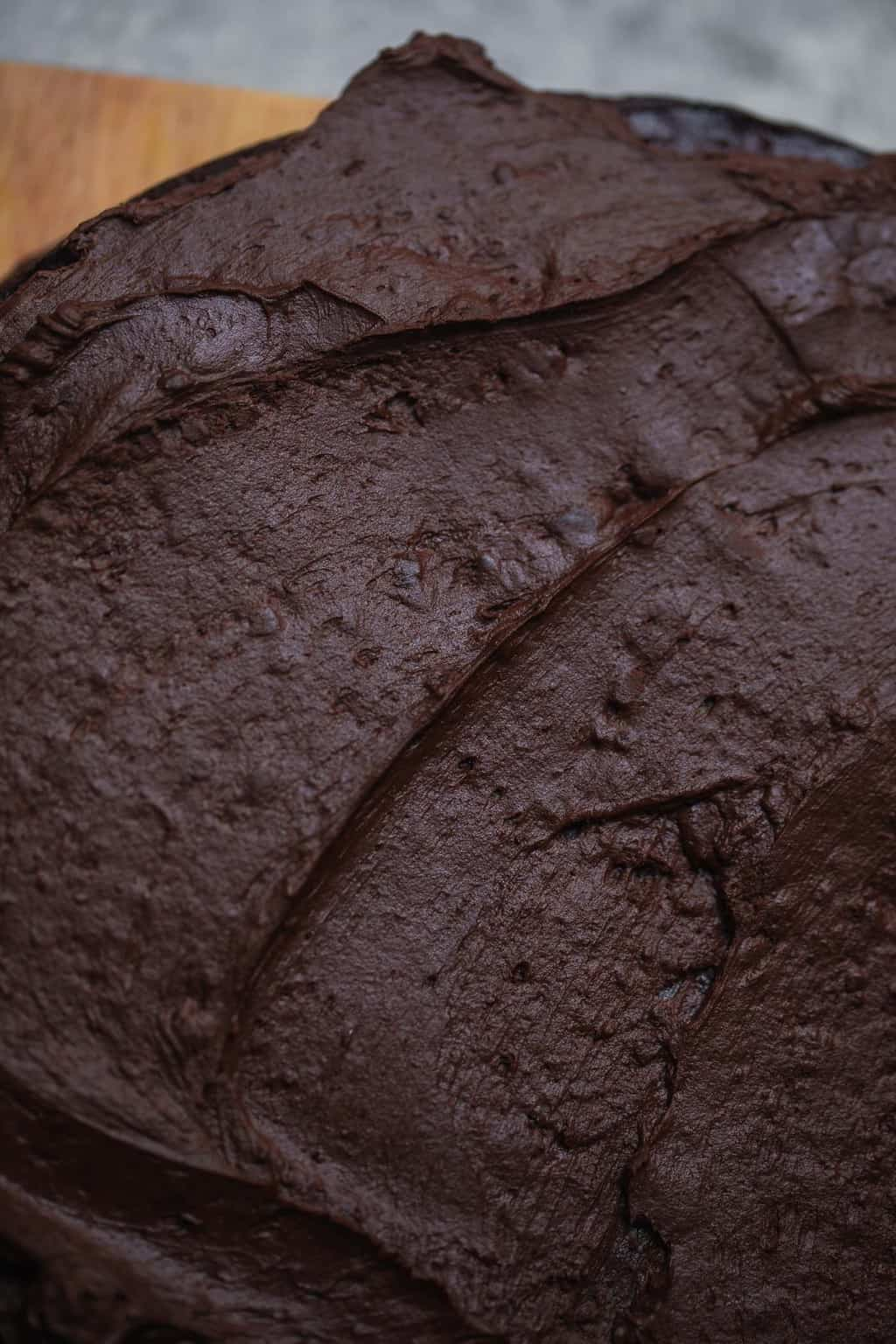 Chocolate frosting being spread on vegan cake