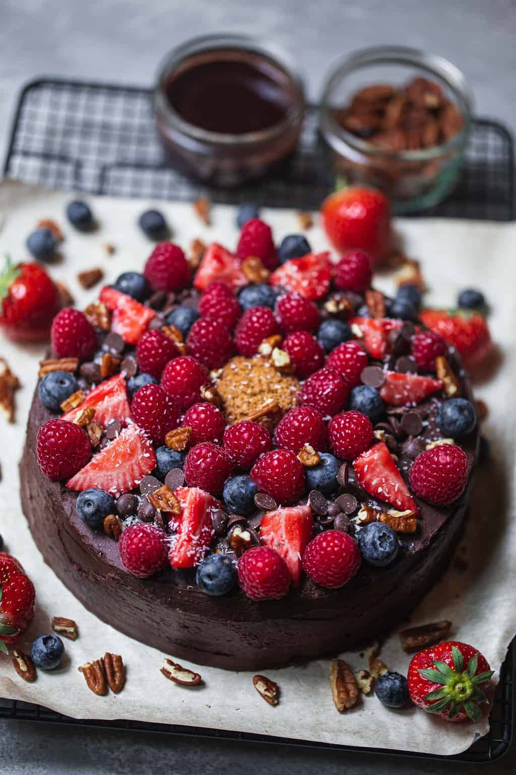 Dairy-free cake with berries on a cooling rack