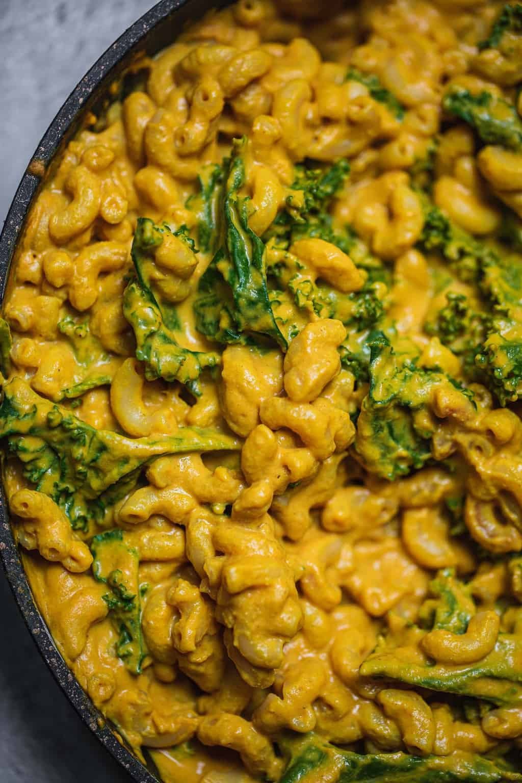 Macaroni pasta with kale in a large frying pan