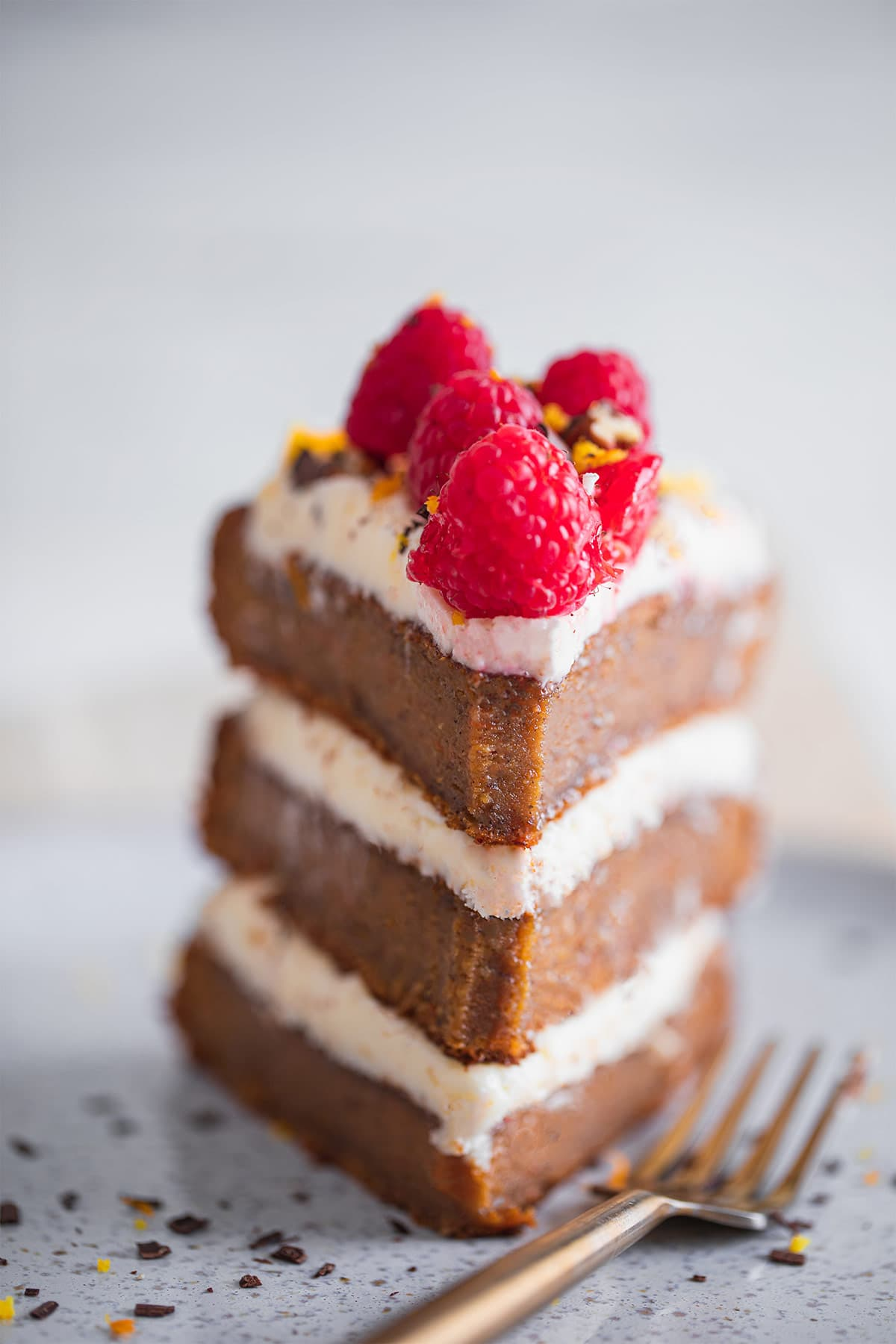 Slice of dairy-free gluten-free carrot cake with raspberries on a plate