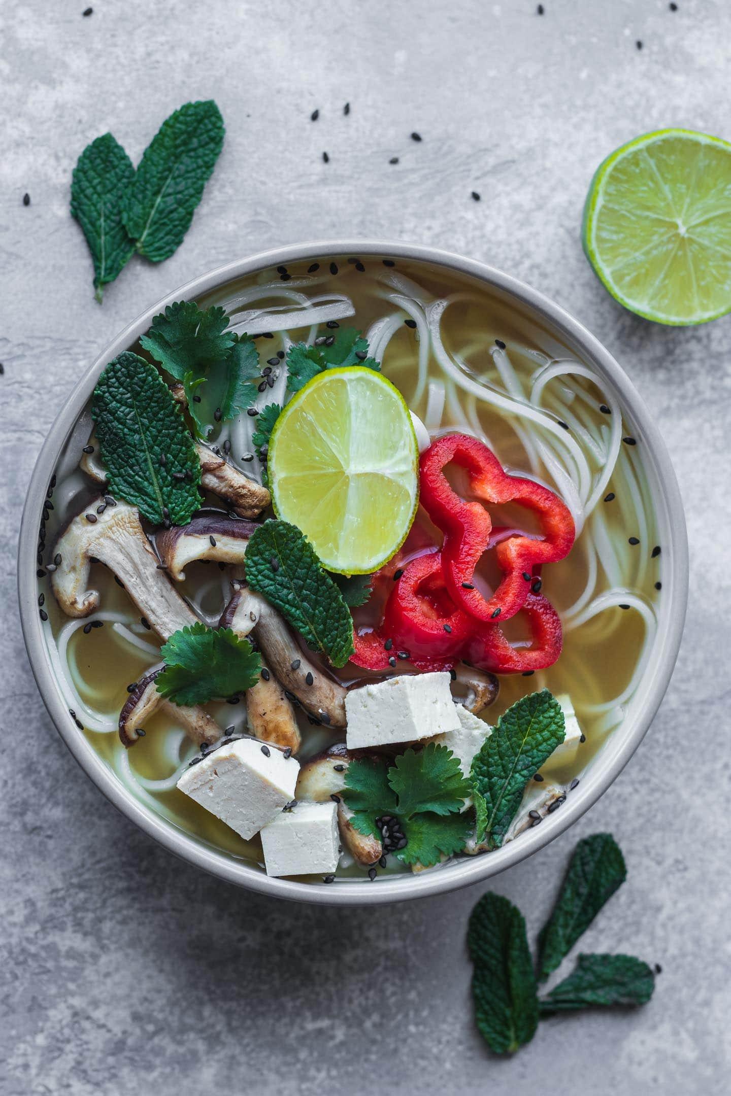 White bowl with vegan pho, shiitake mushrooms and tofu