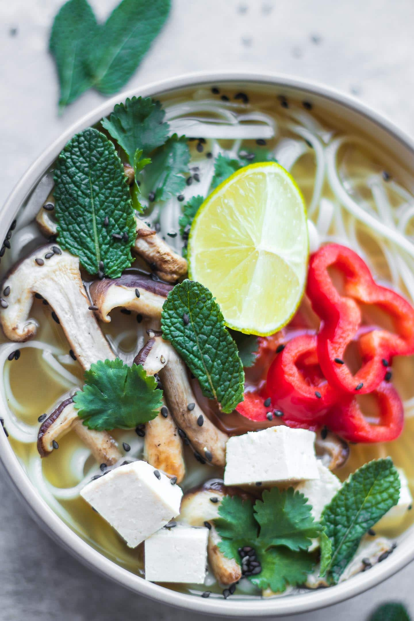 White bowl with vegan pho, shiitake mushrooms and lime