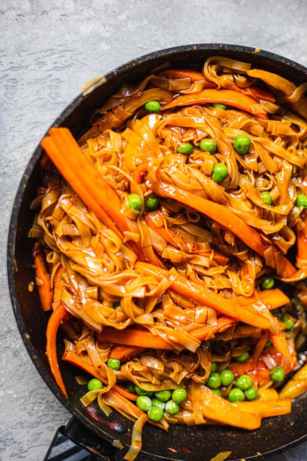 Close up of a frying pan with noodles and vegetables