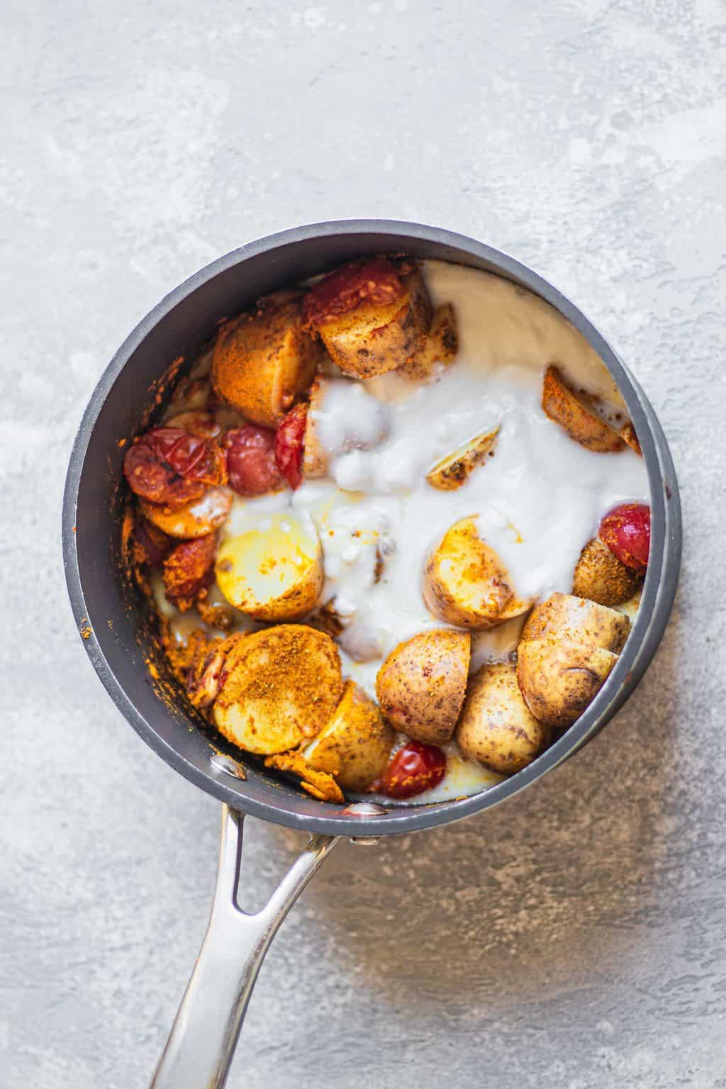 Potato curry ingredients in a saucepan