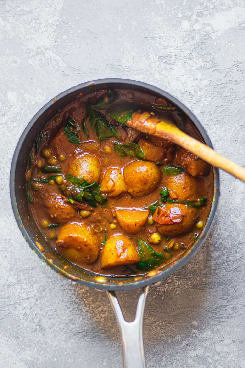 Potato curry with peas in a saucepan