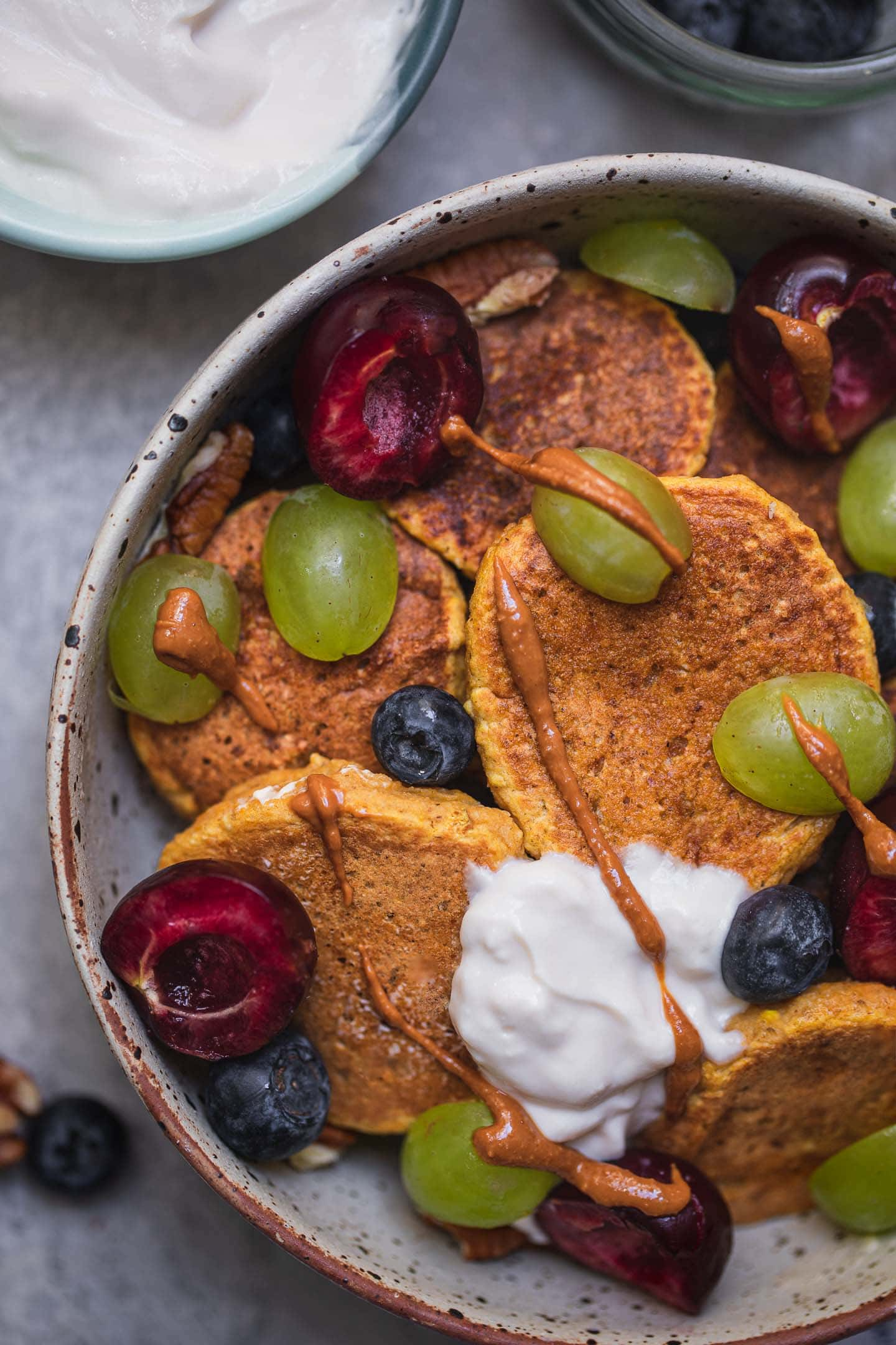 Closeup of a bowl of vegan sweet potato pancakes with soy yoghurt and berries