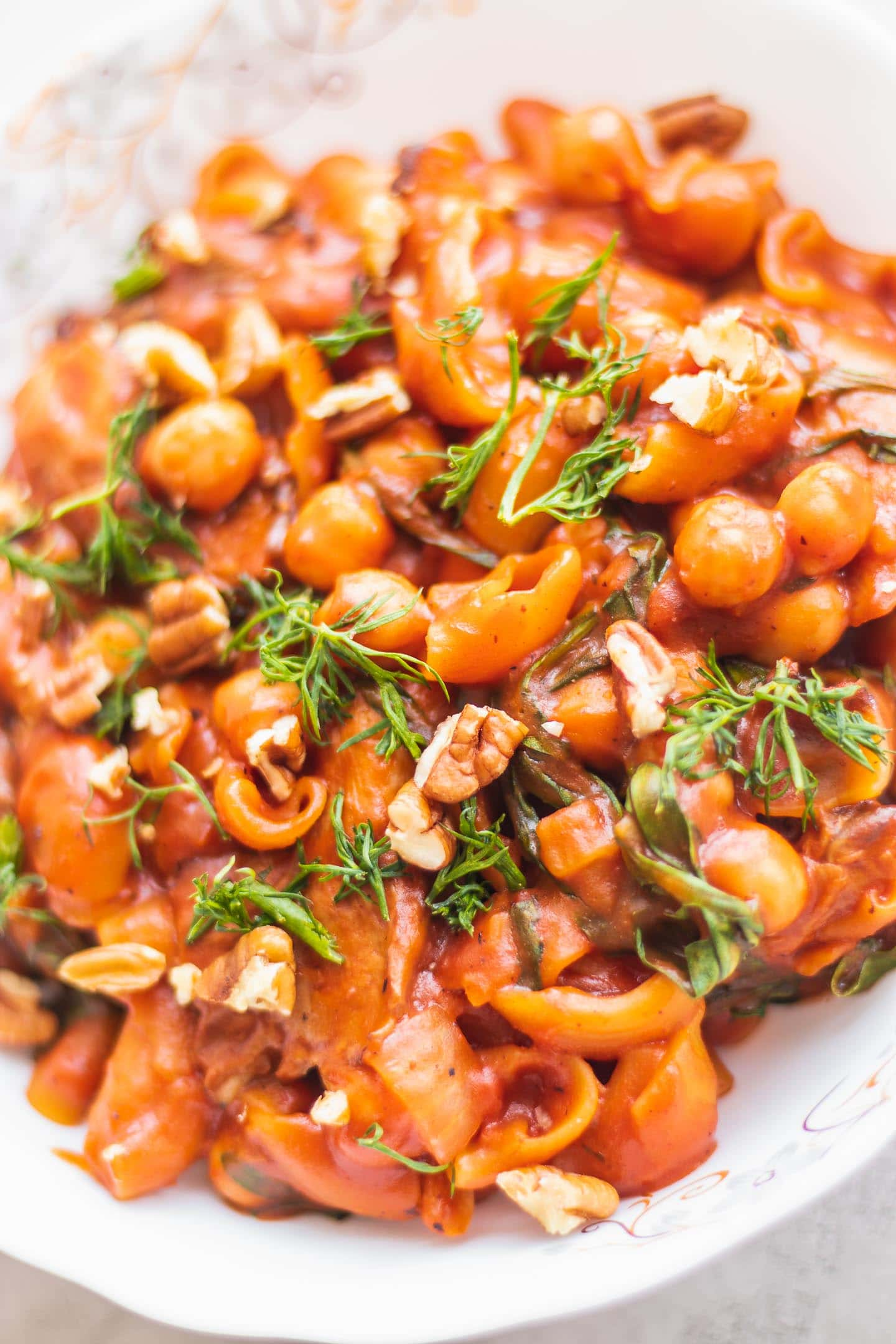 Vegan pasta with chickpeas and oyster mushrooms in a white bowl