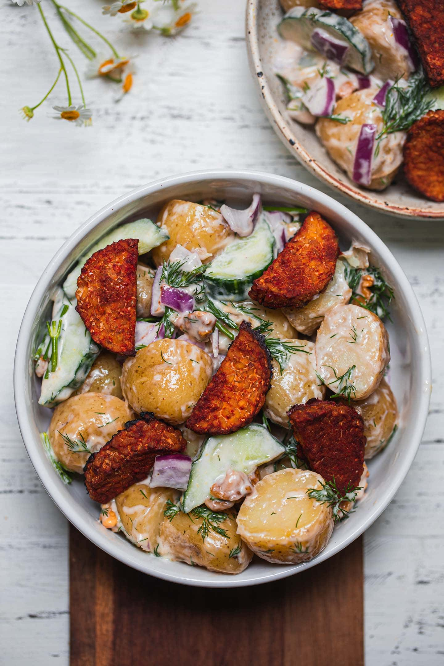 Bowl of a potato salad with vegan mayonnaise and tempeh