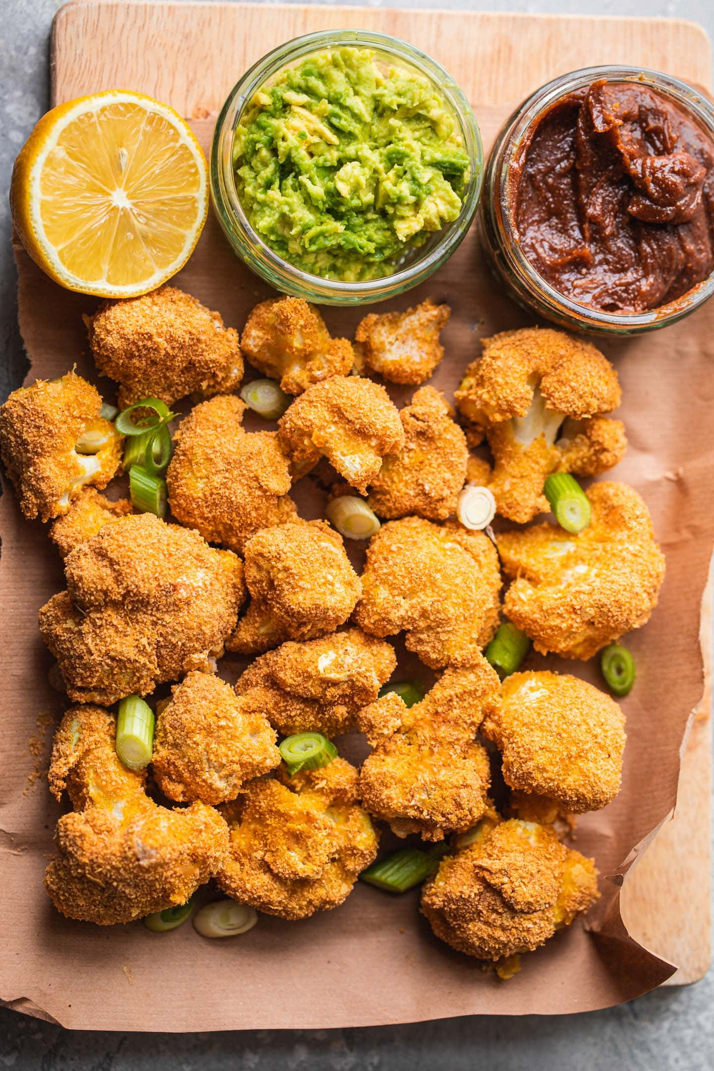 Breaded cauliflower on a wooden board with mashed avocado and almond dip
