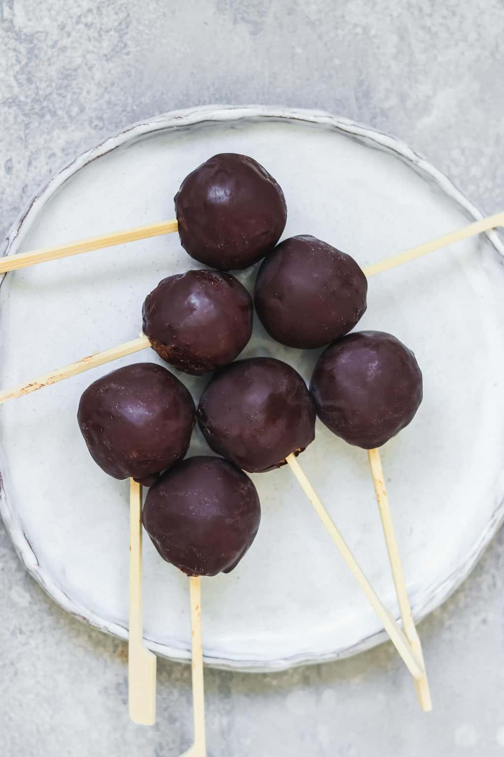 Vegan chocolate-covered cake pops on a white plate
