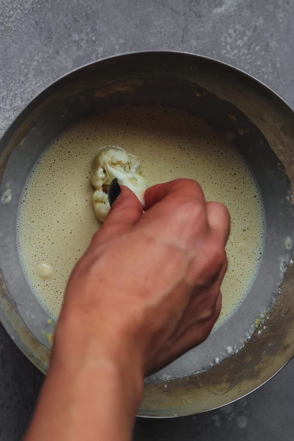 Cauliflower being dipped into batter