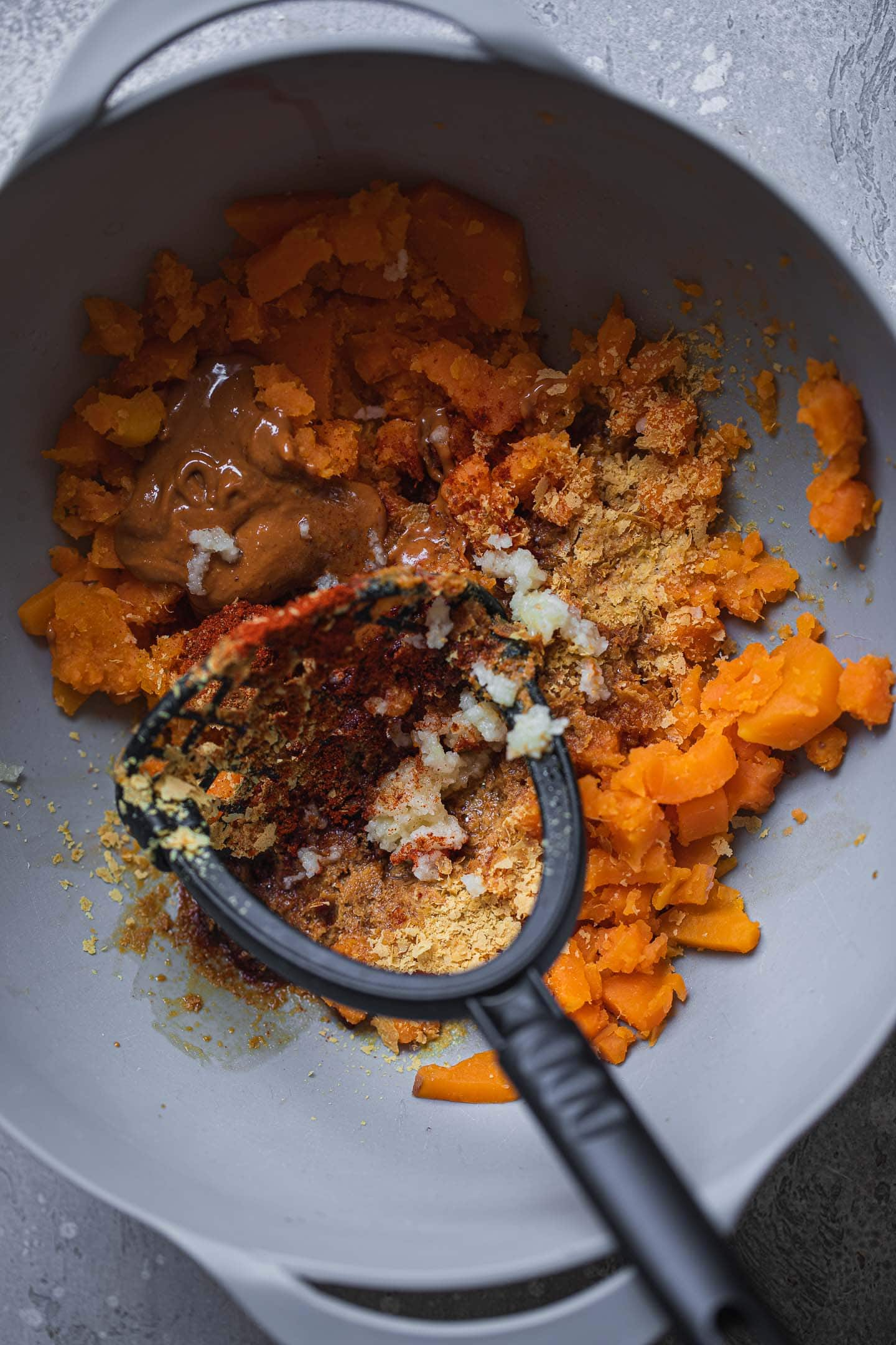 Mashed sweet potato in a mixing bowl