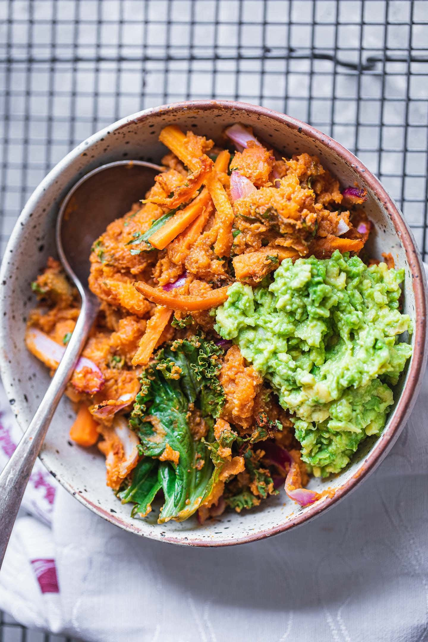 Vegan sweet potato casserole in a bowl with mashed avocado