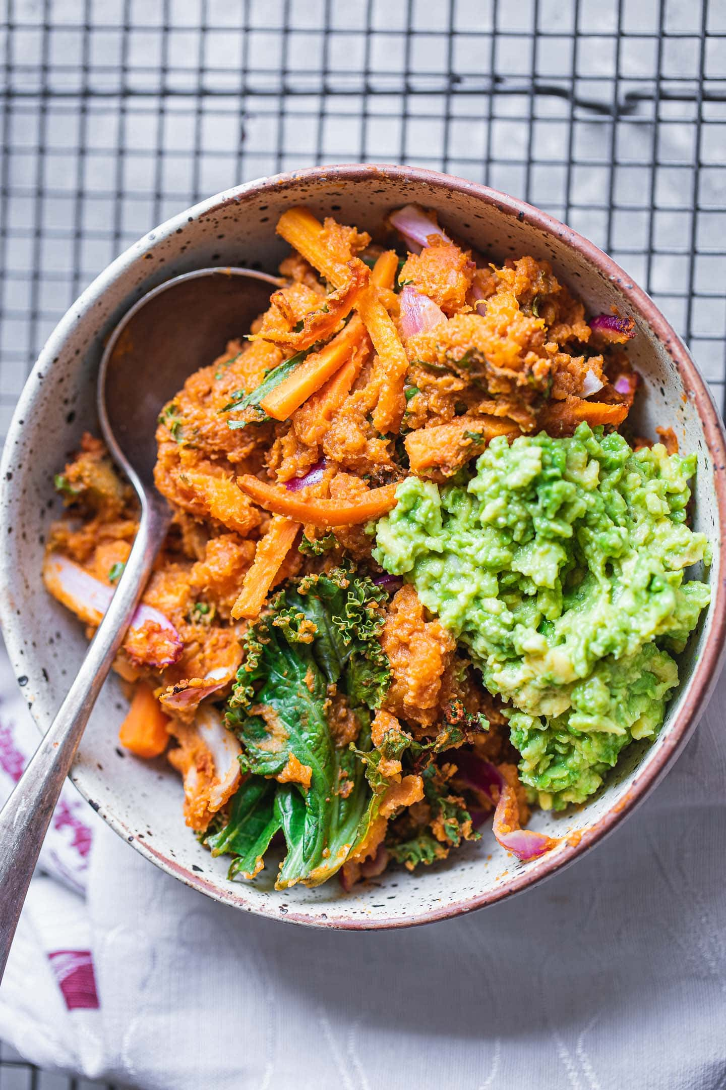 Bowl of a sweet potato casserole with kale and red onion