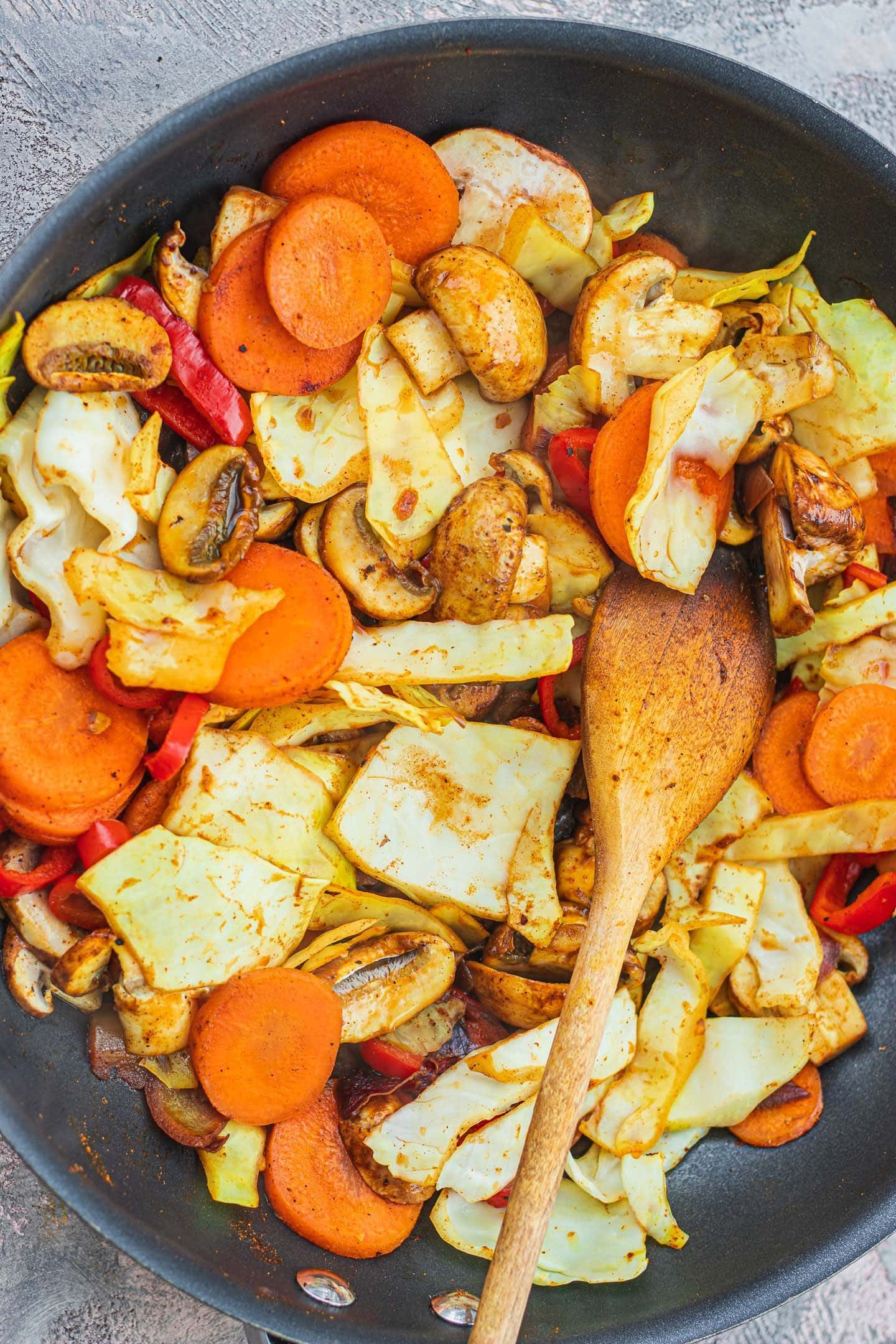 Cabbage, carrot, bell pepper and mushrooms in a frying pan