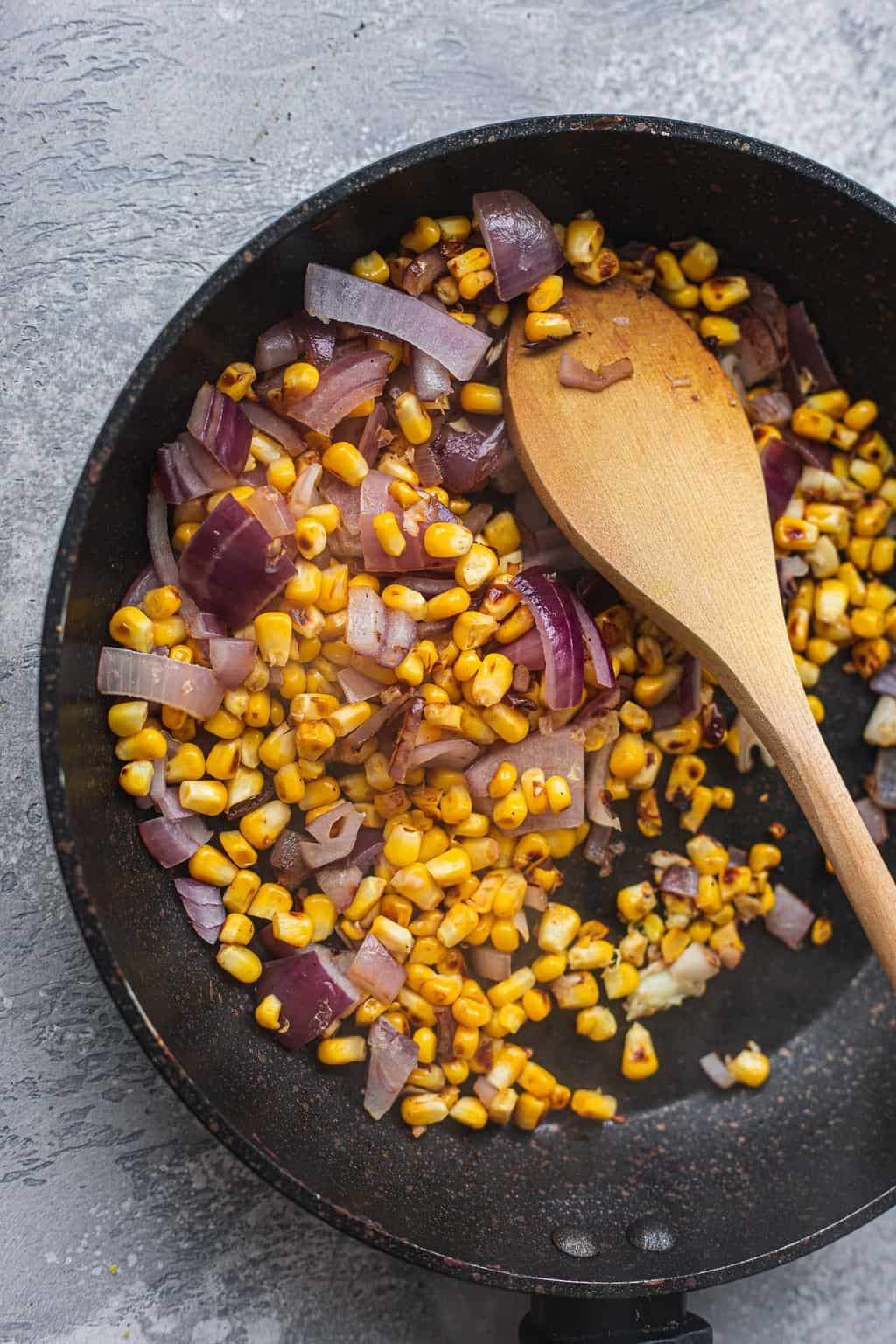 Sweetcorn and red onion in a saucepan